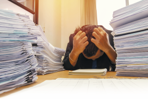 documents on desk stack up high waiting to be managed. Bild: AdobeStock/weerayut