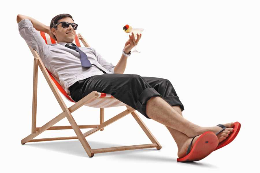 Businessman with a cocktail relaxing in a deck chair isolated on white background Bild: AdobeStock/Ljupco Smokovski