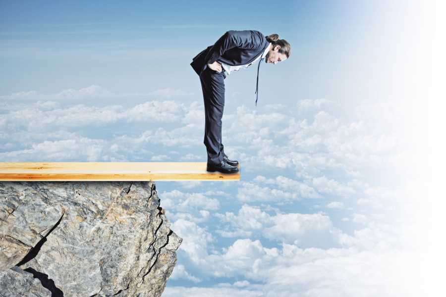 Risk and danger concept. Young businessman looking down from cliff. Sky background Bild: AdobeStock/peshkov